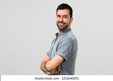 Handsome man keeping arms crossed on grey background