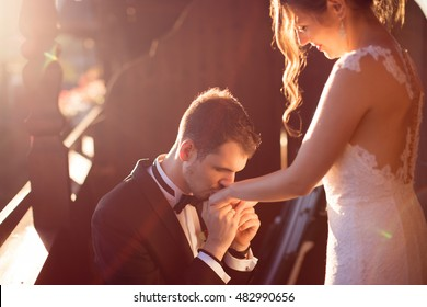 Handsome man kissing hand of his beautiful woman on the balcony during the sunset. Groom and bride on their wedding day