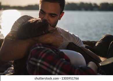 Handsome man kissing and hugging his girlfriend by the river on a sunny day