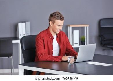 Handsome man with laptop in office