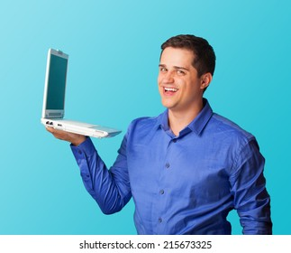 Handsome man with laptop on blue background.