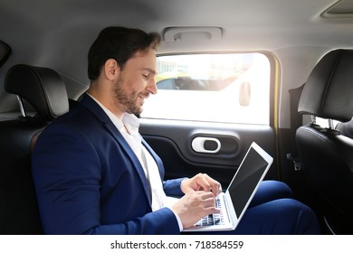Handsome man with laptop sitting in taxi car