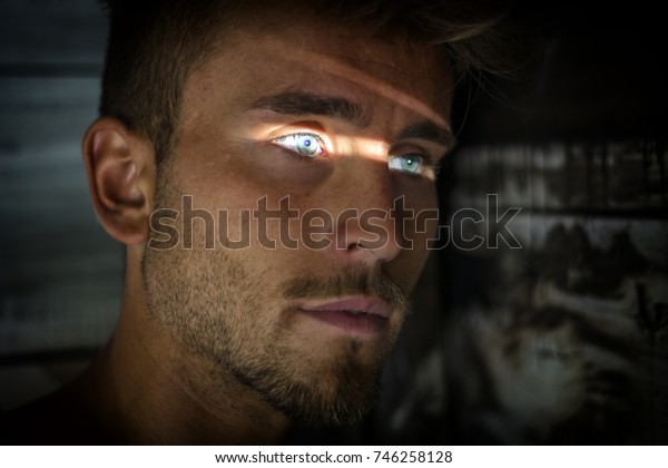 Handsome man leaning against wood planks wall outdoor with slit of light illuminating his blue eyes
