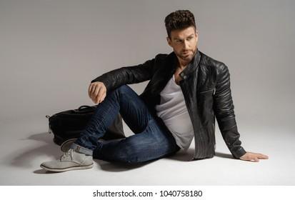 Handsome man in leather jacket posing in studio