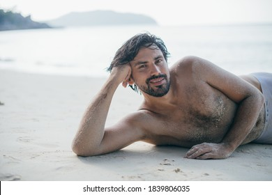 A handsome man lies on the sand by the ocean. Young guy - model posing with a naked torso on a tropical beach. Sexy muscular man. Portrait.