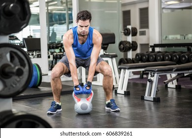 Handsome man lifting kettlebell at the gym
