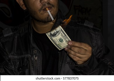 Handsome man lighting his cigar with dollar note. Concept idea.