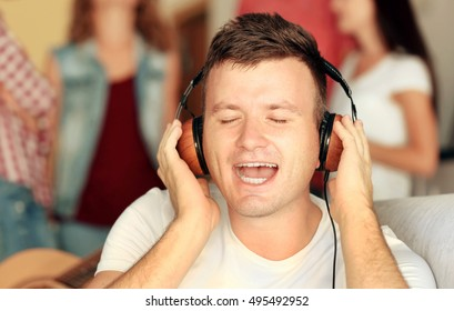 Handsome man listening to music at home