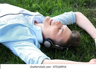 Handsome man listening music on green grass