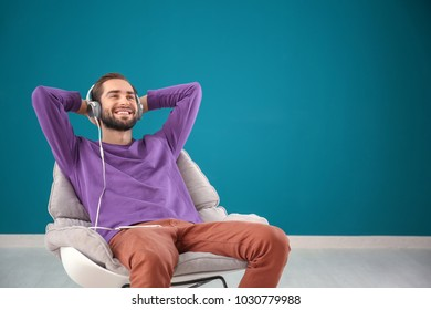Handsome man listening to music while sitting in comfortable armchair against color wall