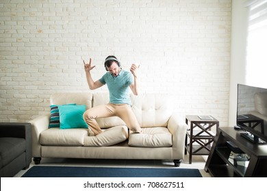 Handsome man listening rock music on his phone and standing on the couch performing the song