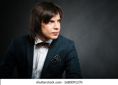 handsome man with long hair brunette and brown eyes in black rim eyeglasses blue suit and red tie sitting and looking forward at black background