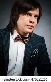 handsome man with long hair brunette and brown eyes in dark suit with stripes and bow tie sitting and looking forward at black background