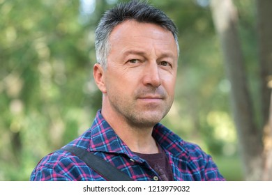 Handsome man looking at camera. Outdoor fall male portrait. Attractive confident middle-aged man in city park.