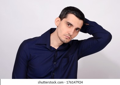 Handsome man looking at camera posing with his hand up. Portrait of a young business man wearing a dark blue shirt.