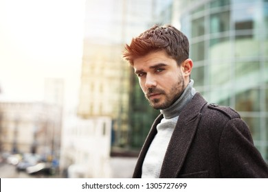 handsome man looking with confidence to camera, outside with office buildings in background