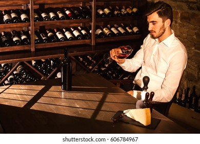 Handsome man looking at glass of wine and smiling. Man sitting by the table in a wine vault.