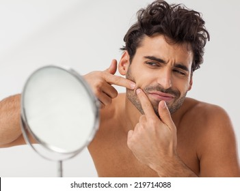 Handsome man looking at himself in the bathroom mirror. Squeezing pimple.