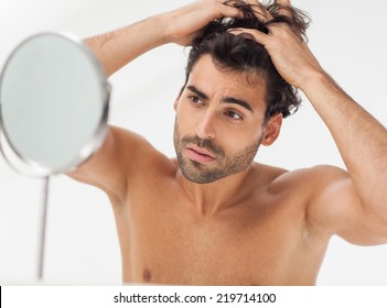 Handsome man looking at himself in the bathroom mirror. Checking for gray hair.