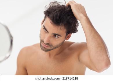 Handsome man looking at himself in the bathroom mirror.