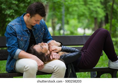 Handsome man looking in his girlfriend's eyes while she is laying on a bench in park