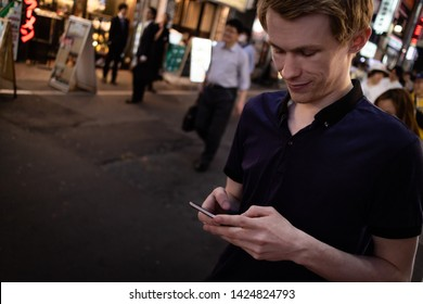 A handsome man looking at his phone on a Tokyo street