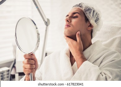 Handsome man is looking into the mirror and examining his chin while sitting at the cosmetician