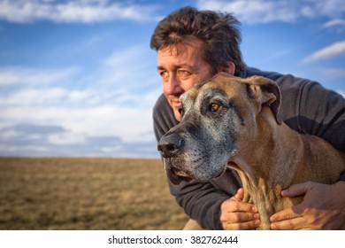 Handsome man looking left into distance with his great Dane in field with blue sky