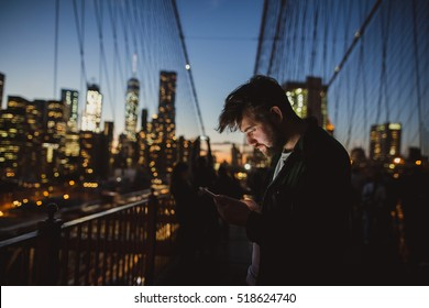 Handsome man looking at mobile phone at Brooklyn Bridge at night. Amazing view of New York on the background.