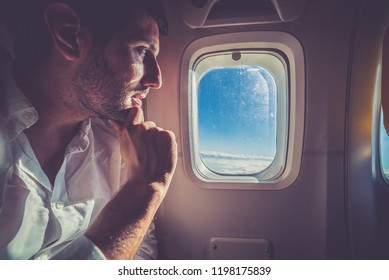 handsome man looking out through window of the airplane during beautiful blue sky day