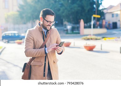 Handsome man looking at the phone while walking down the street