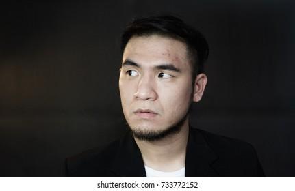 Handsome man is looking something in dark background
