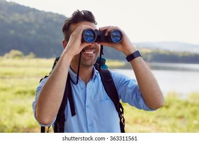 Handsome man looking through binoculars during hiking adventure