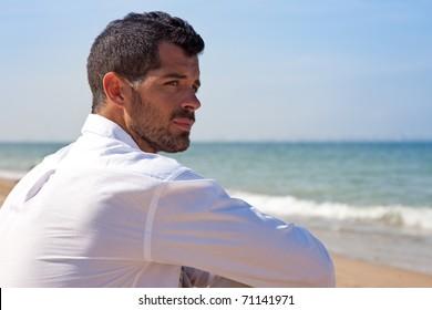 Handsome man looking worried in front of the ocean