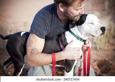 Schöner Mann mit liebevoller und schöner Hundekuh auf dem Arm des Menschen tätowieren