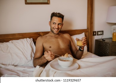 Handsome man lying on bed, happy smile drink orange juce in the morning. Attractive guy smiling in bedroom at home, sexy young male model