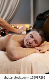Handsome man is lying on the couch while being massaged at a spa salon