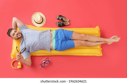 Handsome man lying on inflatable mattress against color background