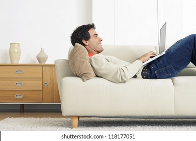 Handsome man lying on sofa and working on his laptop