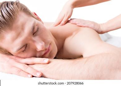 Handsome man lying in a spa salon enjoying a deep tissue back massage.