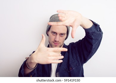 Handsome man making frame with his hands on gray background