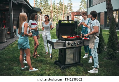 Handsome man is making grill barbecue. Group of friends are having bbq party outdoors on the backyard.