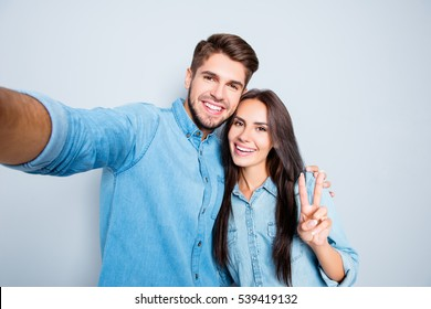 Handsome man making selfie with his pretty woman gesturing v-sign