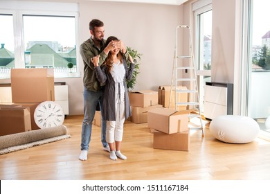 Handsome man making a surprise for his girlfriend in the form of the new apartment, moving in concept