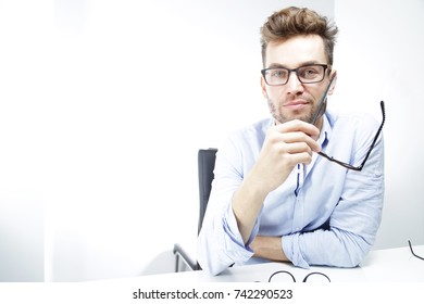 Handsome man  with many eyeglasses. White man holding a pair of eyeglasses.