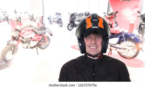 handsome man with a motorbike helmet at a motorcycle and scooter shop