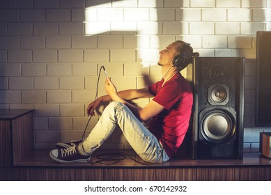 Handsome man, a music lover listens to music with headphones with a mobile phone in a modern interior against the media and large speakers. Enjoying music is fun and communicates on Internet at home