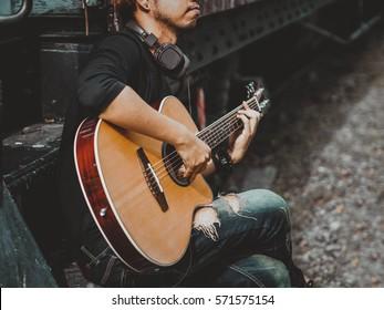 ギターを弾くハンサムな男性音楽家