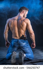 Handsome man with naked muscular torso holding hand gun, on dark smoky background, seen from the back