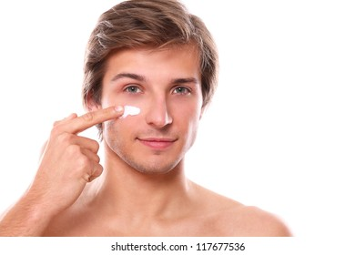 Handsome man with naked torso smiling and applies cream on his face